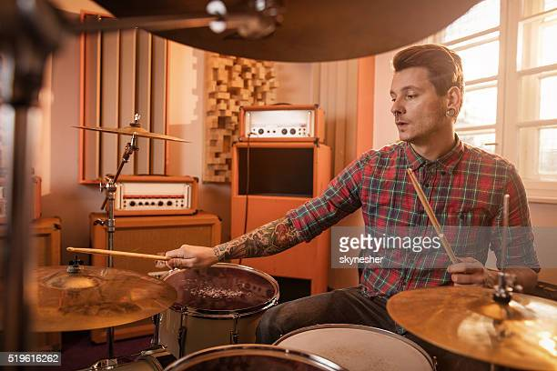 Joven tocando música de los tambores en el estudio.