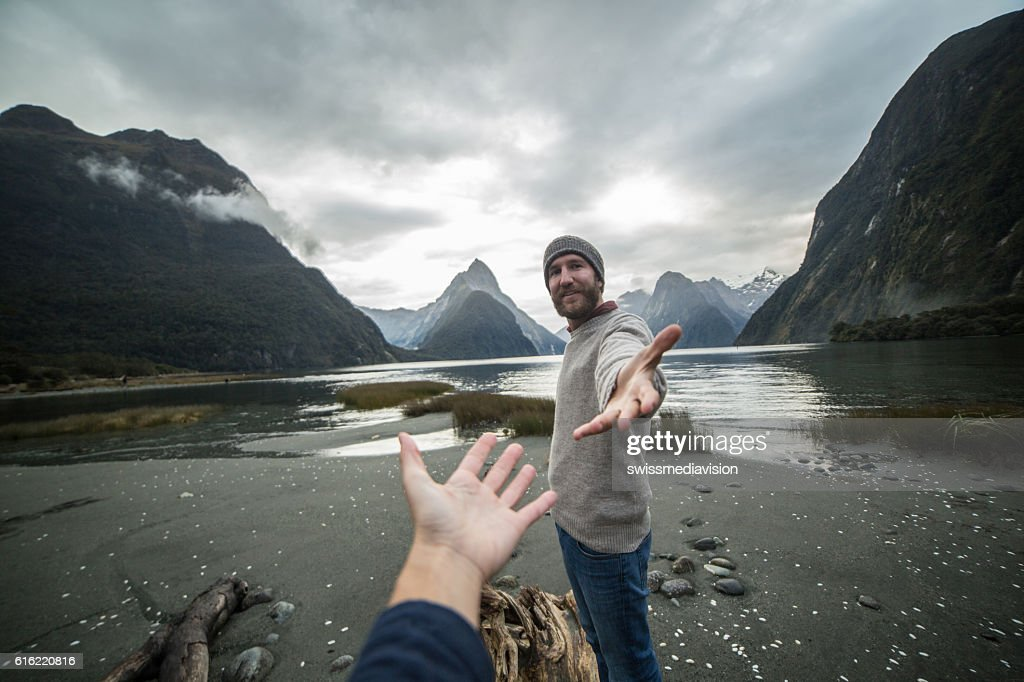 Young man in nature offers hand to partner : Stock Photo