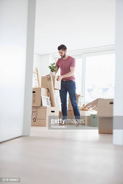 Young man in new flat unpacking cardboard boxes