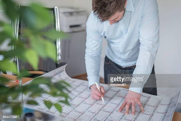 young man in office looking at calendar - frist stock-fotos und bilder