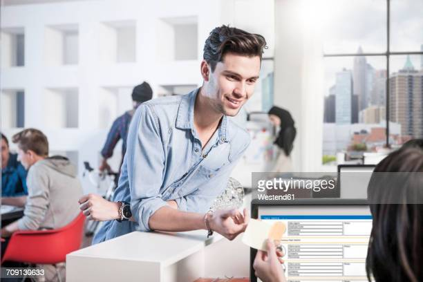 Young man in office smiling at female colleague