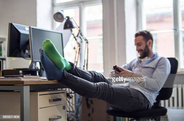 Young man in office with feet on desk wearing different socks