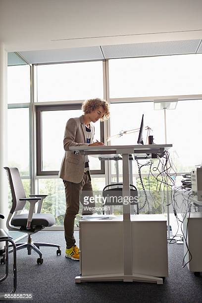Young man in office working at adjustable desk