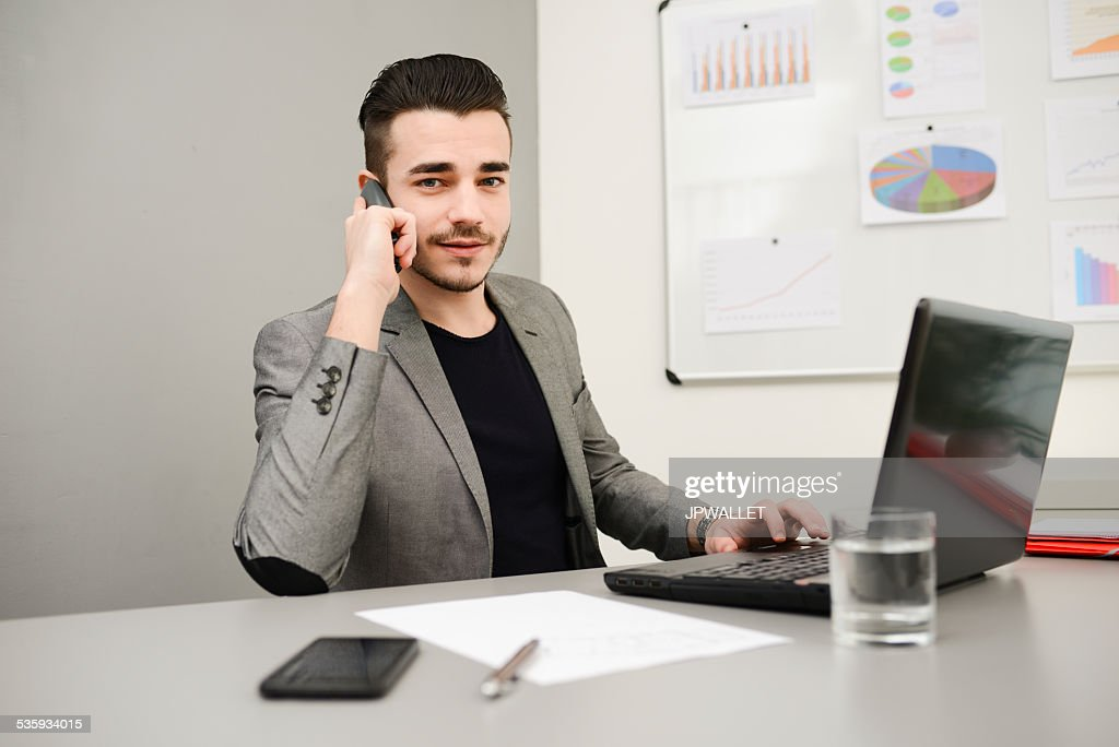 young man in office working on laptop computer and phone : Stock Photo