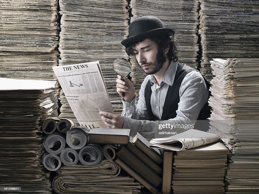 Young man in old fashioned costume doing research among newspapers : Stock Photo