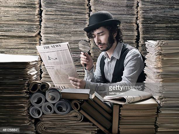 young man in old fashioned costume doing research among newspapers - detective stock pictures, royalty-free photos & images