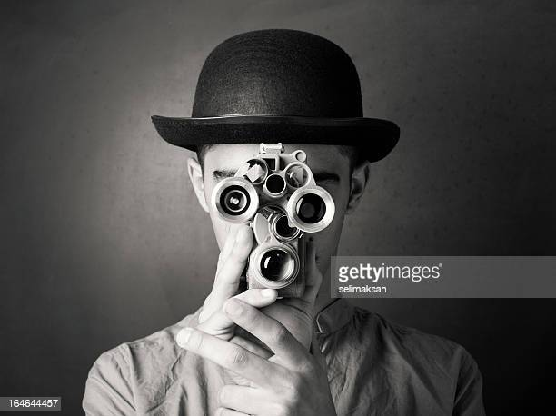 young man in old fashioned style filming via antique camera - black and white stock pictures, royalty-free photos & images
