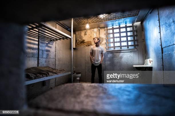 jongeman in de oude gevangenis cel gezien door deur slot - gevangeniscel stockfoto's en -beelden