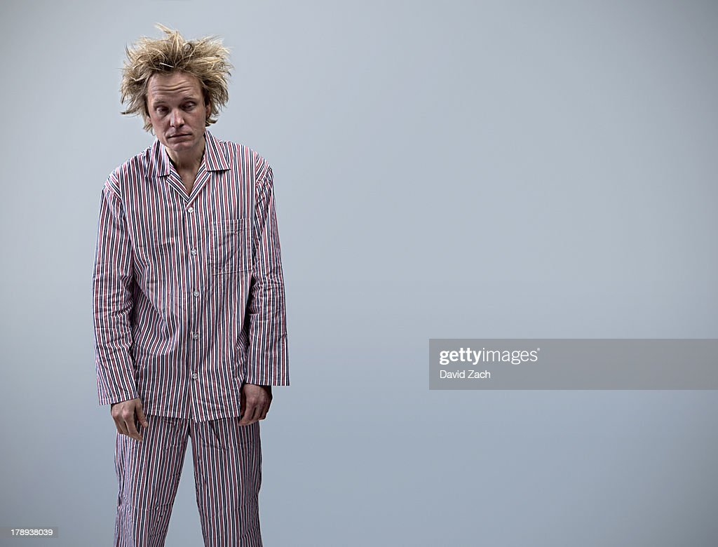 Young man in pajamas looking tired, portrait : Stock Photo