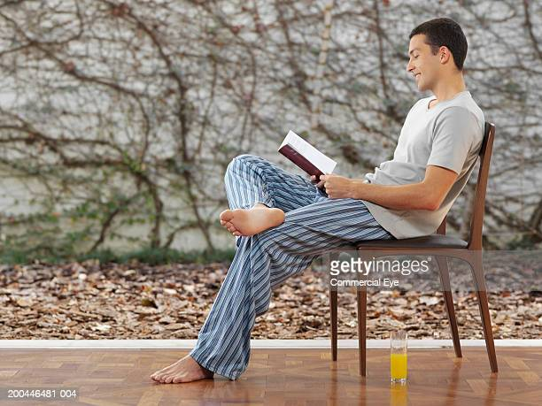 young man in pajamas reading book, side view - 足を組む ストックフォトと画像