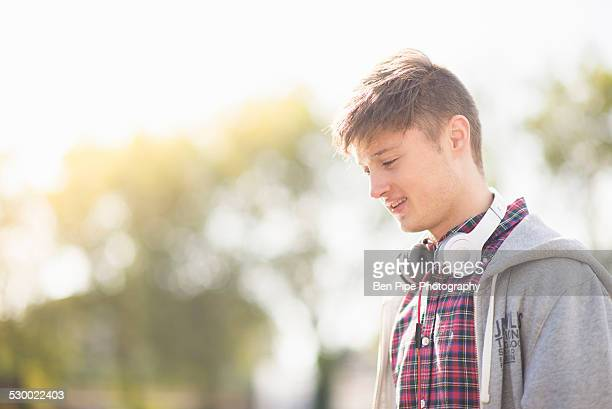Young man in park with headphones around his neck