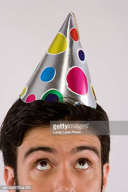 Young man in party hat, close-up, looking up