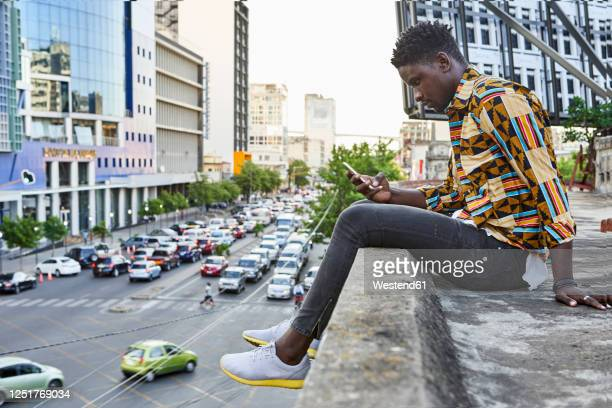 young man in patterned shirt sitting on roof terrace in the city checking his phone, maputo, mozambique - mozambique stock pictures, royalty-free photos & images
