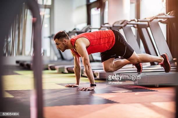 Jeune homme en position de planche, exercice dans la salle de sport.
