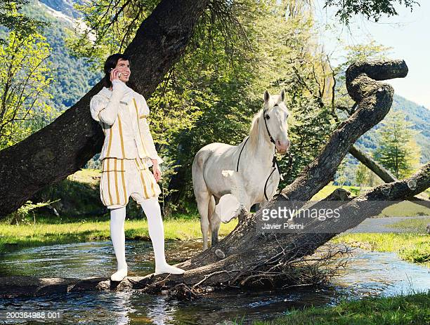 Young man in prince costume using cell phone beside horse and river