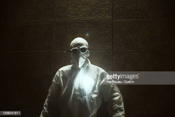 young man in protective workwear standing against wall - chernobyl stock pictures, royalty-free photos & images