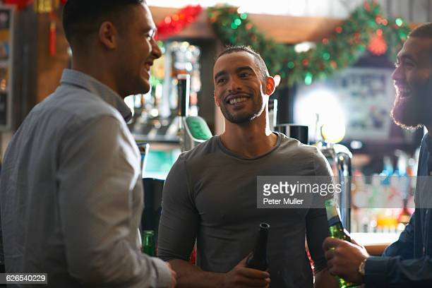 Young man in public house holding beer bottle looking at friend smiling