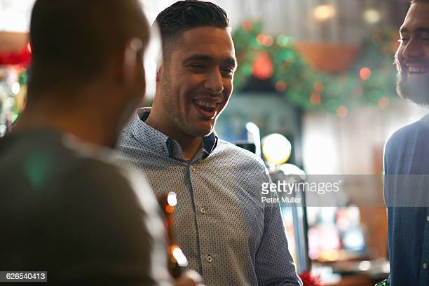 Young man in public house with friends smiling