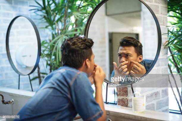 young man in public restroom checking the face on the mirror - brufoli foto e immagini stock