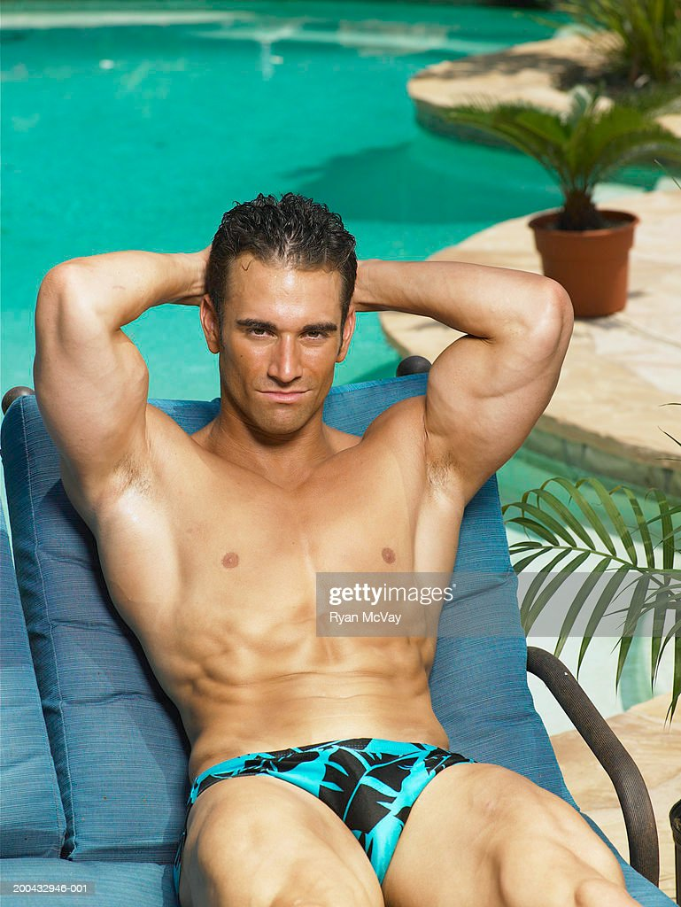 Young man in racing briefs sitting beside pool, hands behind head : Stock Photo