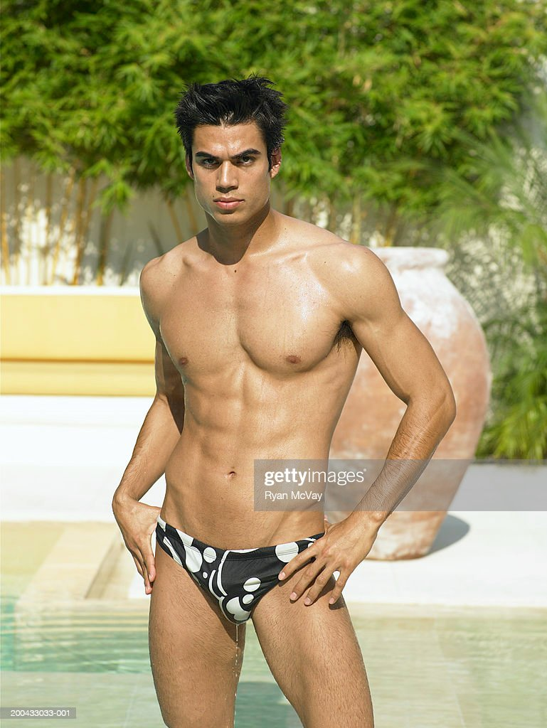 Young man in racing briefs standing beside pool, hands on hips : Stock Photo