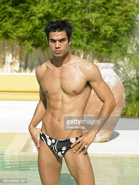 young man in racing briefs standing beside pool, hands on hips - young men in speedos stock photos and pictures