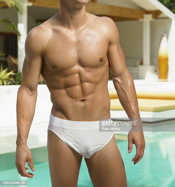 Young man in racing briefs standing beside pool, mid section