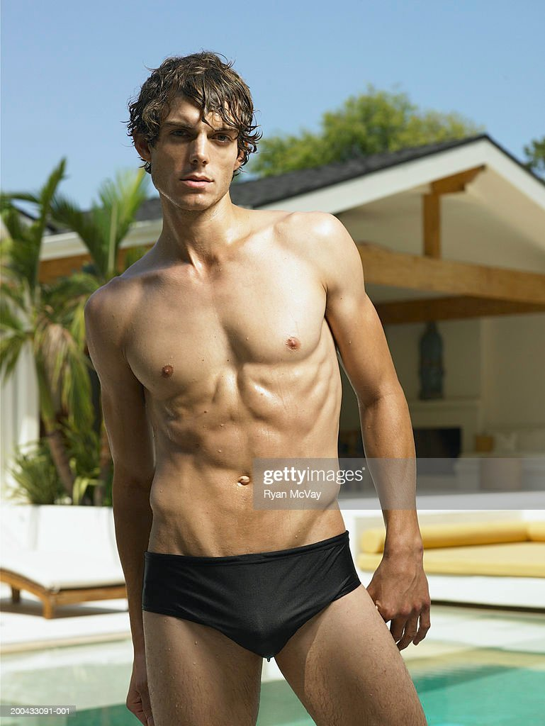 Young man in racing briefs standing beside pool, portrait : Stock Photo