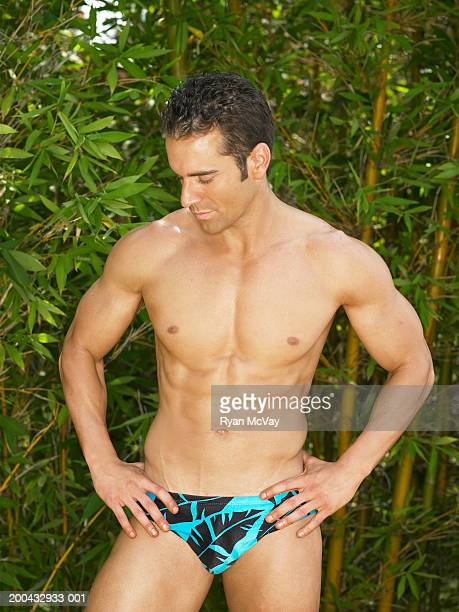 young man in racing briefs standing with hands on hips, looking down - young men in speedos stock pictures, royalty-free photos & images