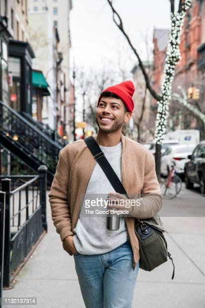 young man in red cap walking down city street - brooklyn new york stock-fotos und bilder
