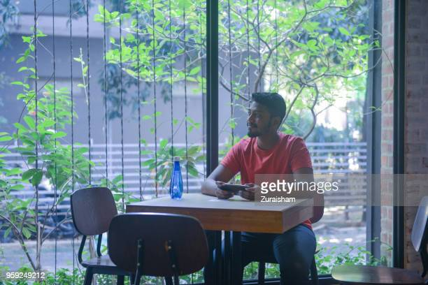 Young man in red shirt social networking at a restaurant on his cell phone or sending a text message at a cafe