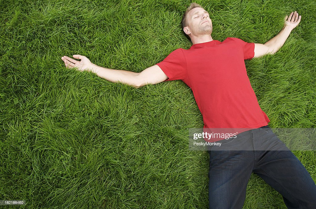 Young Man in Red T-Shirt Relaxing on Green Grass : Stock Photo