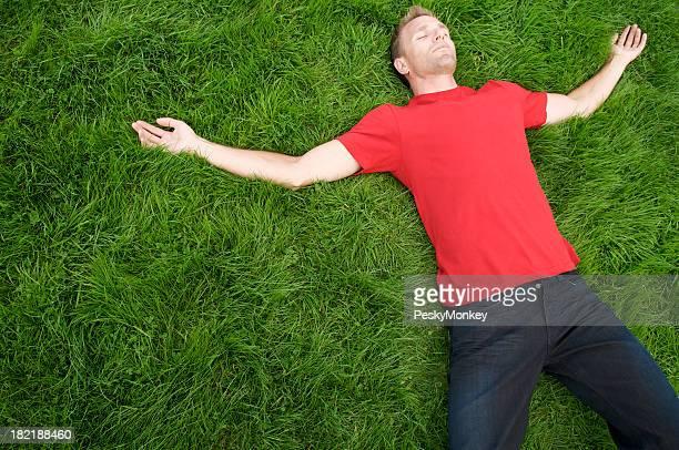 若い男性レッドの T シャツでリラックスした緑の芝生