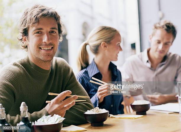 Young man in restaurant with woman and man, smiling, portrait
