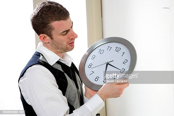 Young man in room, adjusting clock, side view