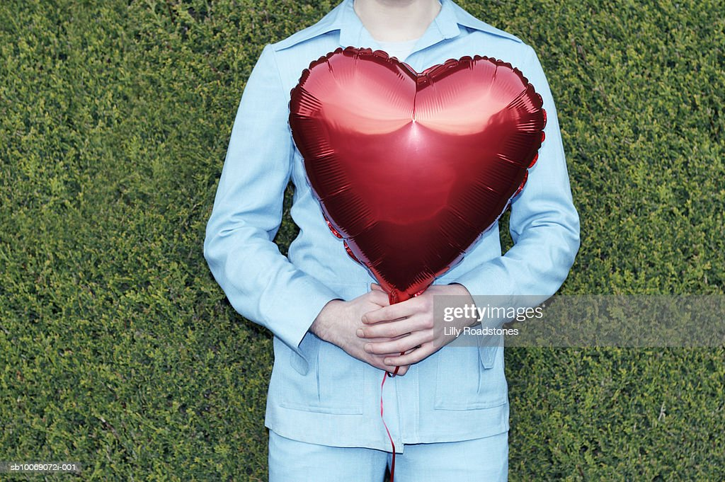 Young man in safari suit holding red heart shaped balloon, mid section : Stockfoto