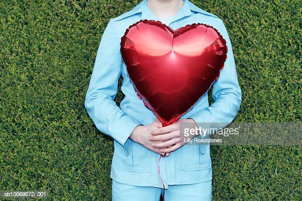 Young man in safari suit holding red heart shaped balloon, mid section
