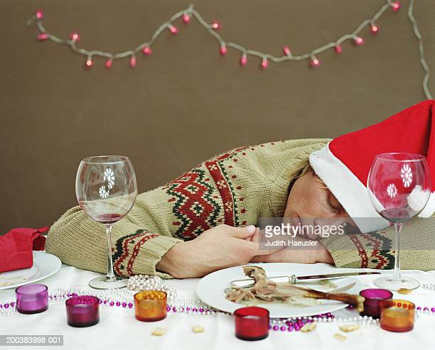 young man in santa hat sleeping at dinner table, resting head on arm - headwear stock pictures, royalty-free photos & images