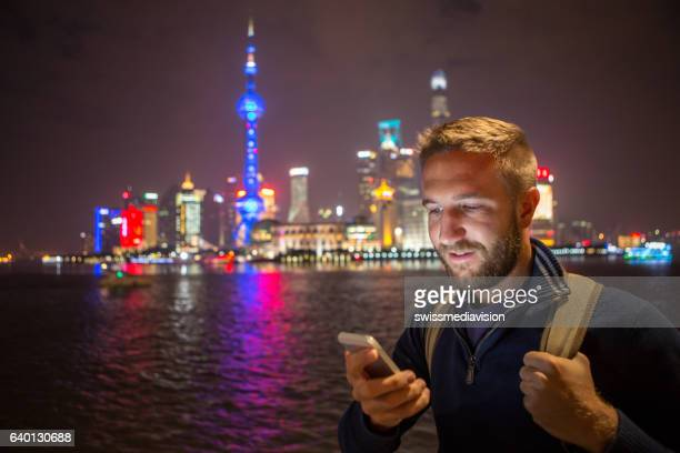 Young man in Shanghai text messaging on mobile phone, night