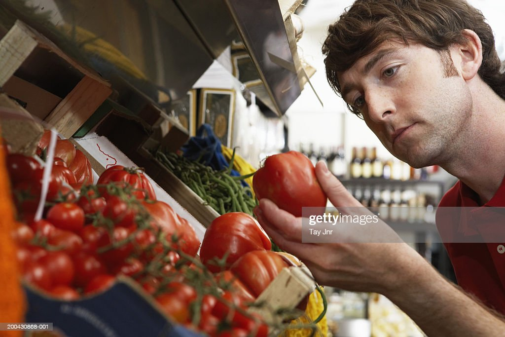 Young man in shop examining large tomato, close-up : Stock Photo