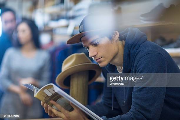 Young man in shop reading magazine