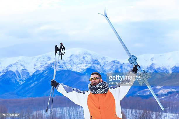 Young man in snow mountain-hands up holding ski and poles