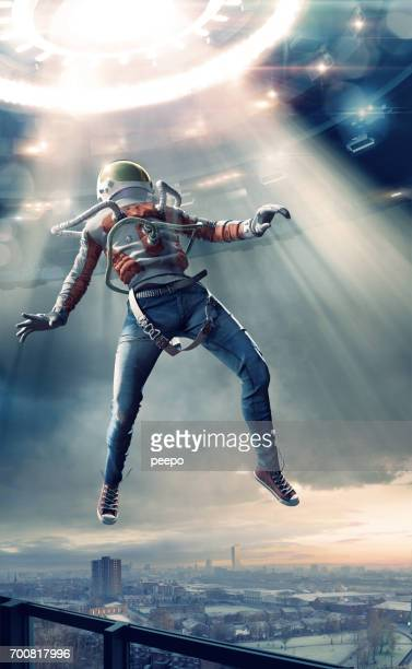 young man in spacesuit levitating in light towards ufo - alien stock photos and pictures