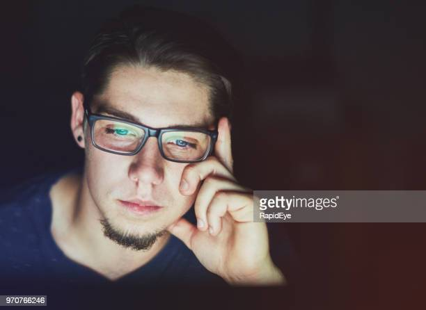young man in spectacles works late on computer - goatee stock pictures, royalty-free photos & images