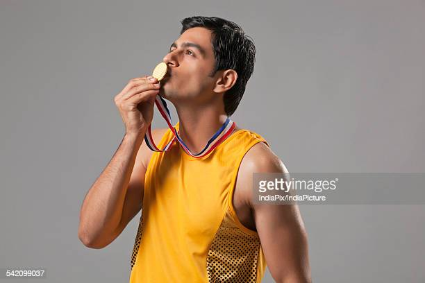 Young man in spots wear kissing gold medal isolated over gray background