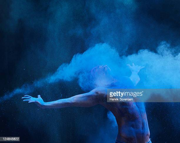 Young man in spray of colored powder