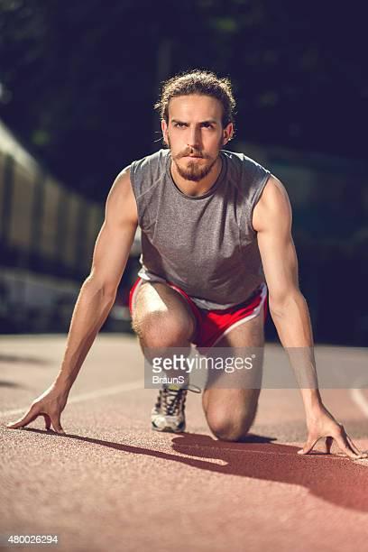 hombre joven en la posición inicial en pista de deporte. - línea de salida fotografías e imágenes de stock