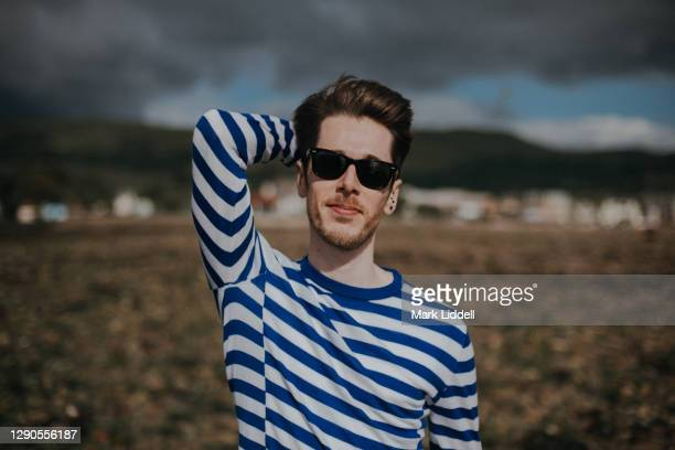 young man in striped sweater standing on the beach, largs, scotland - river clyde stock pictures, royalty-free photos & images