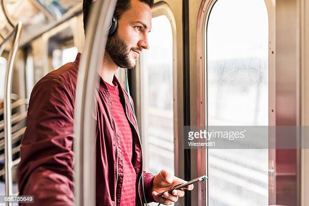 Young man in subway wearing headphones