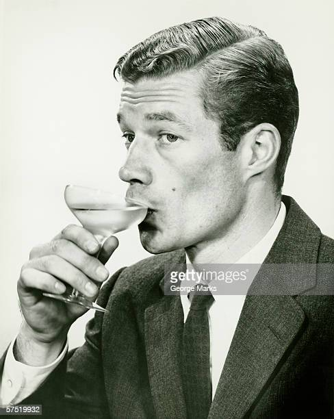 young man in suit, drinking wine (B&W), portrait
